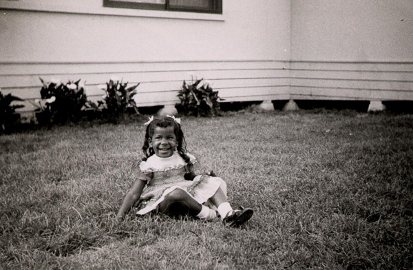 Mom as a toddler sitting on front lawn